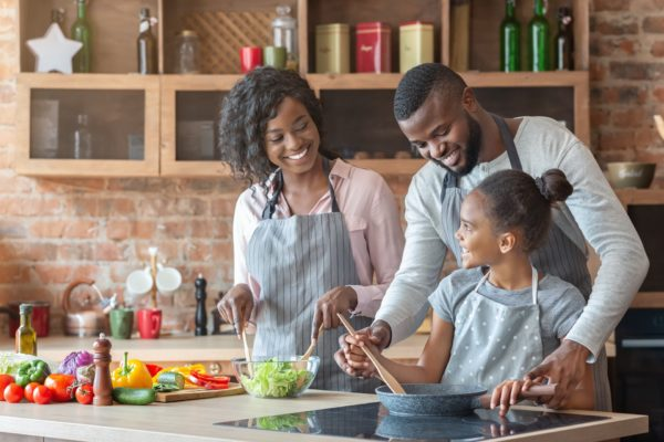 Kind black parents teaching their adorable daughter how to cook healthy food, kitchen interior, copy space