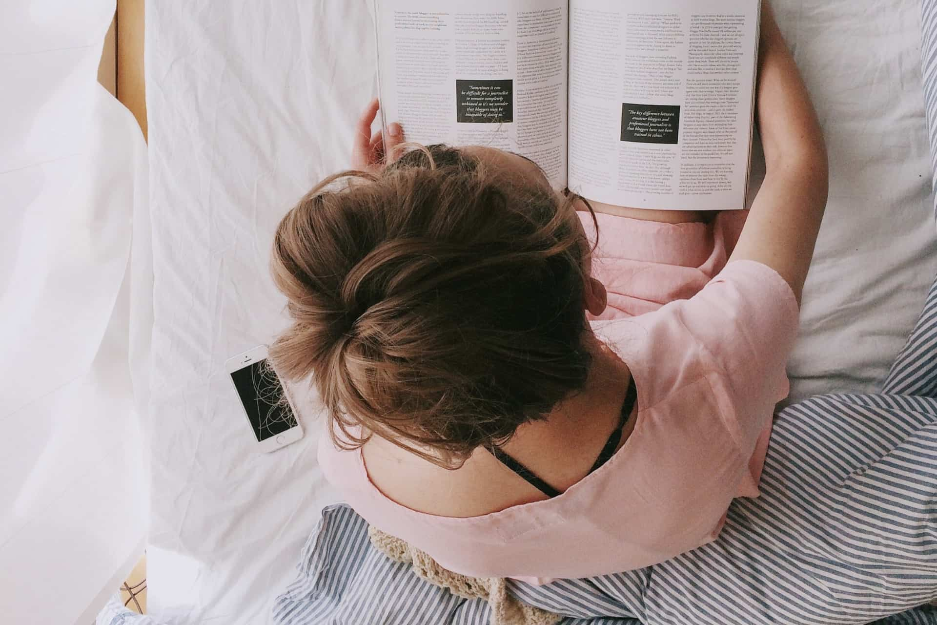 woman in pink dress sitting on bed while reading 698158 - 5 ways to relax and reconnect with yourself during quarantine